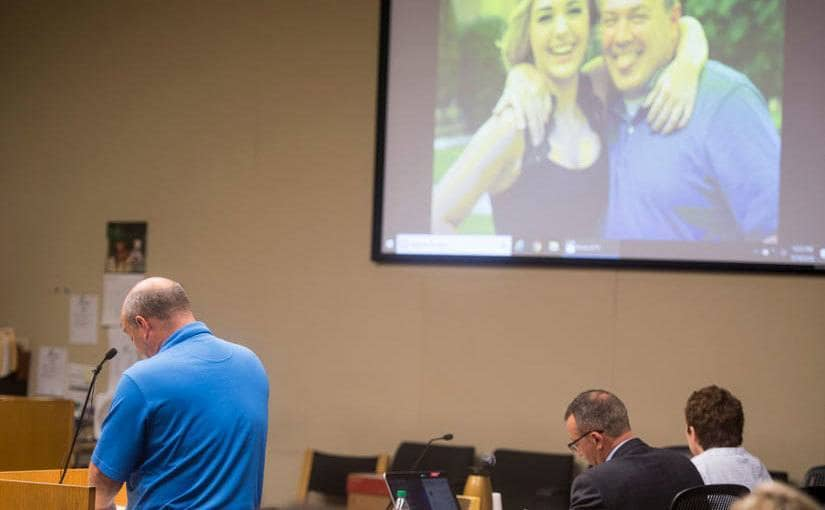 Photos of Emma Jane Walker are shown on a screen as Emma's father Mark Walker gives a victim impact statement.