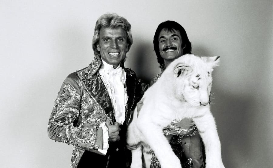 Siegfried Fischbacher and Roy Horn posing for a promotional photo with a white tiger.
