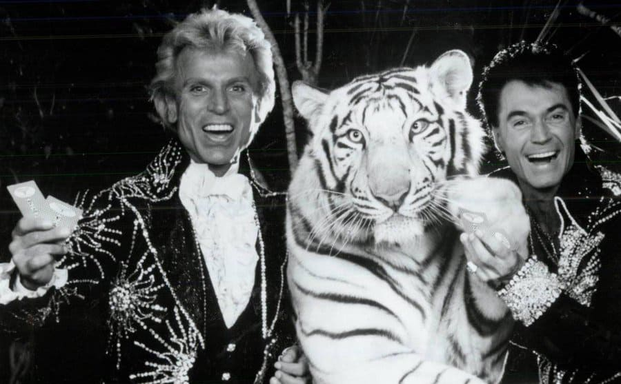 Siegfried and Roy at a casino table with a large tiger.