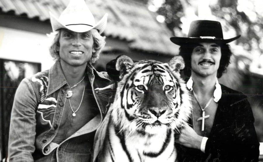 Siegfried and Roy petting a full-grown tiger that sits between them.