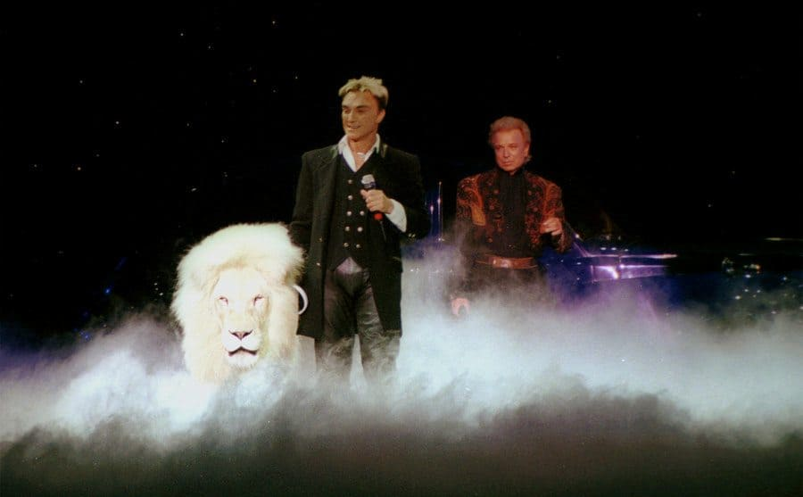 Siegfried and Roy performing onstage with a lion.