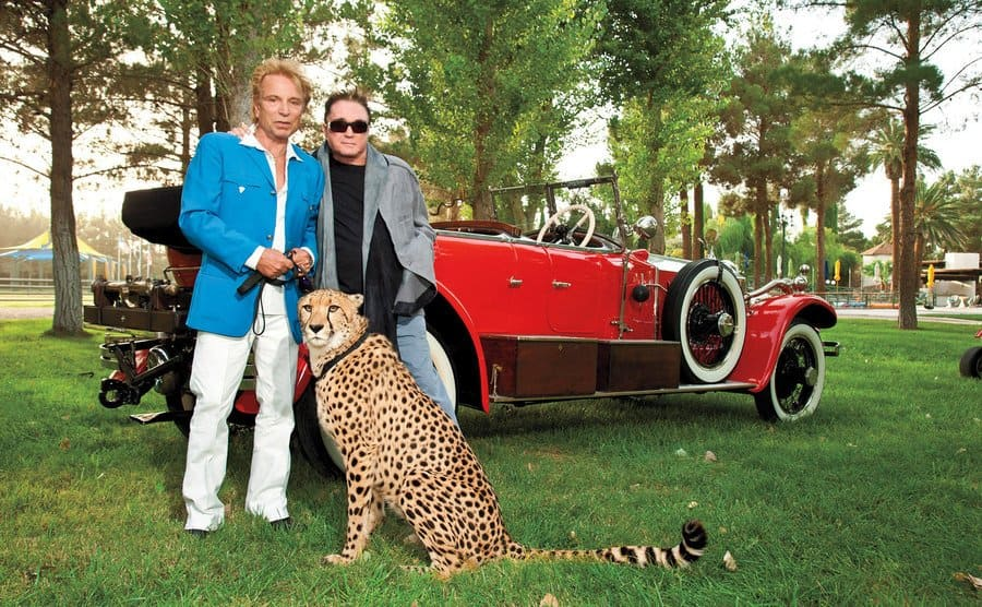 Siegfried and Roy pose with a leopard in front of a vintage red car.