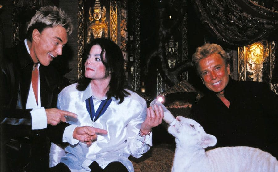 Michael Jackson with Siegfried and Roy and a tiger cub.
