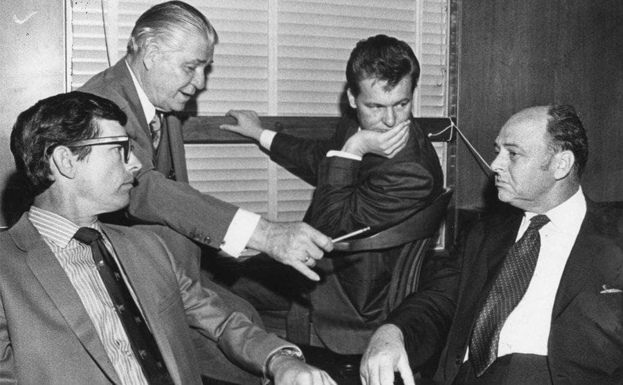 Charles V. Harrelson moments after pleading not guilty in the murder of Houston carpet executive Alan Harry Berg, confers with Percy Foreman and other attorneys.