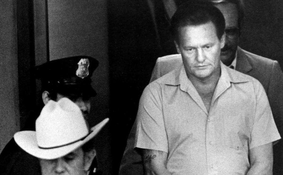 Charles Harrelson being escorted by a cop and detectives while handcuffed.