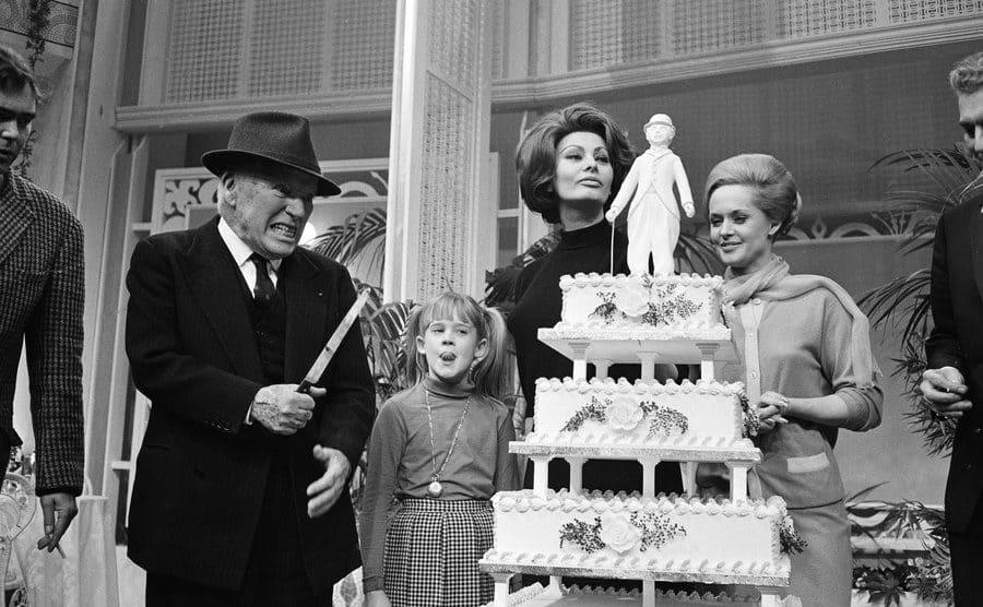 Charlie Chaplin, Melanie Griffith, Sophia Loren, and Tippi Hedren standing around a tall cake celebrating Chaplin's birthday
