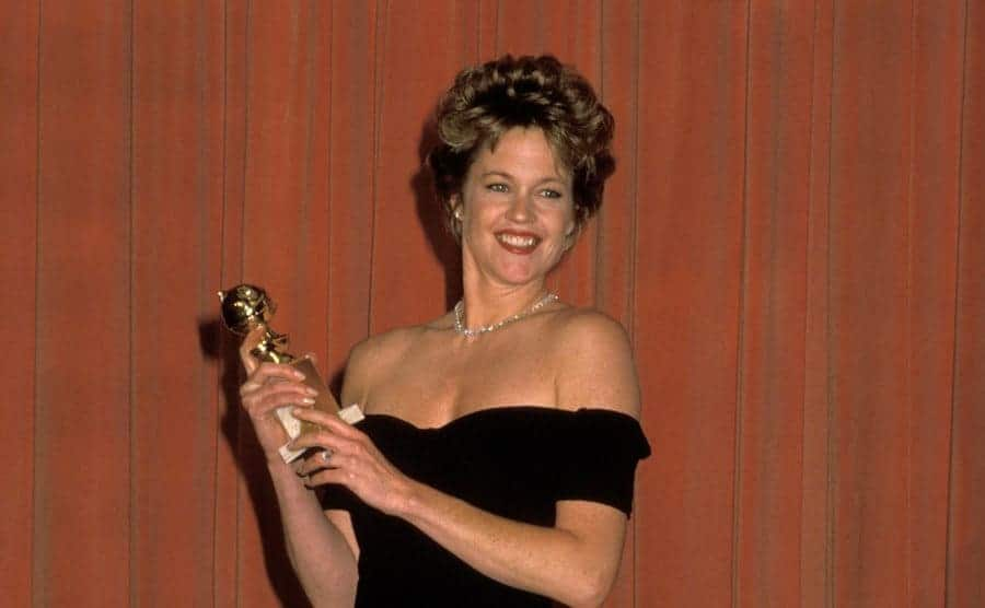 Melanie Griffith holding a Golden Globe Award