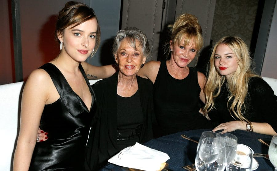 Melanie Griffith with Tippi Hedren, Dakota Johnson, and Stella Banderas sitting around a table at a restaurant