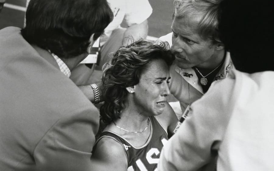 Mary Decker is helped by olympic workers after being tripped up by Zola Budd