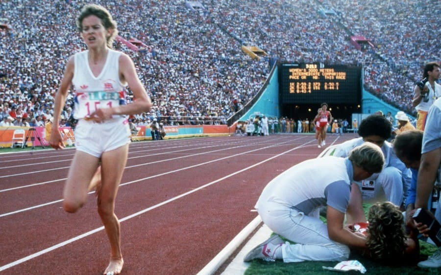 Mary Decker is attended to on track as Zola Budd runs the track