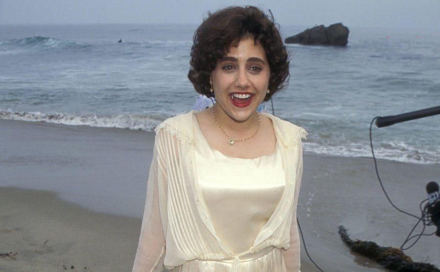 Brittany Murphy dressed in a creamy silk dress at the beach attending the Clueless Malibu Premier circa 1995.