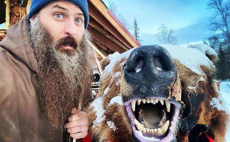 Matt is posing next to a wild bear.