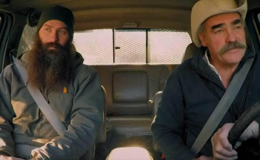 Matt is sitting next to Marty as he drives a van
