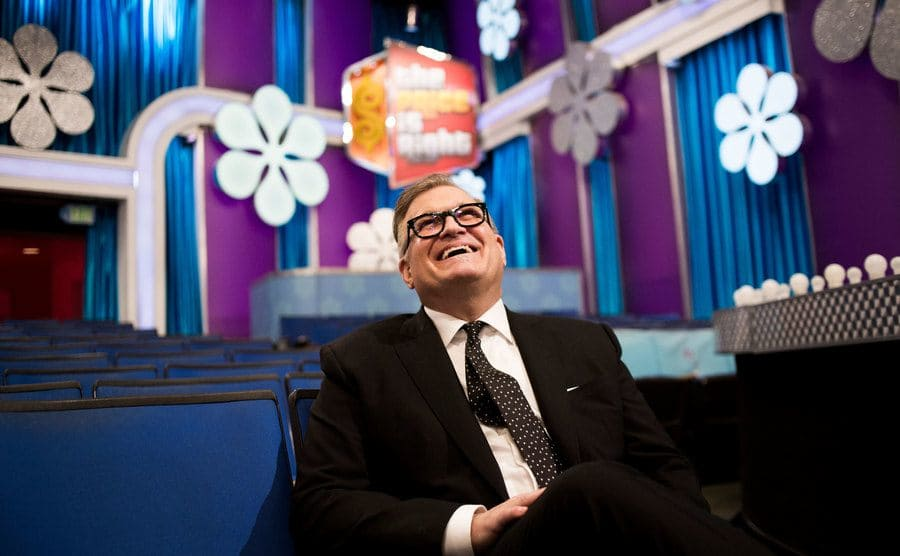 Drew Carey is sitting on a theater seat used for the show on the CBS lot in Los Angeles.