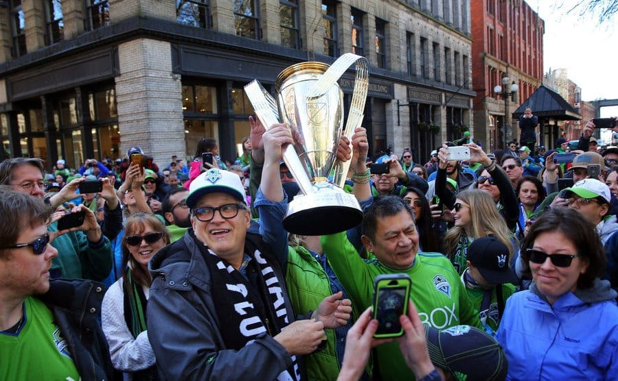 Drew Carey and Sounders fans hold up the MLS Cup during the march to match before the Sounders season opener game.