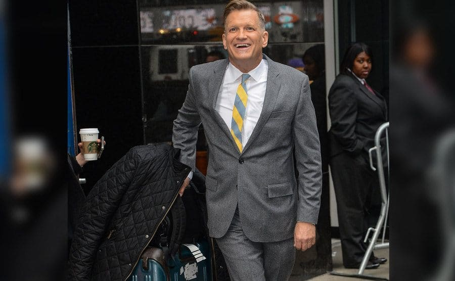 Drew Carey is carrying his suitcase.