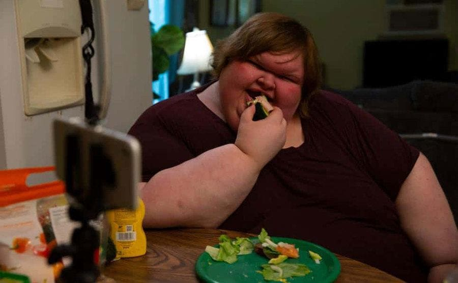 Tammy is filming herself eating a salad in the kitchen.