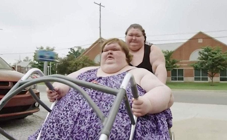 Amy pushes Tammy in her wheelchair.