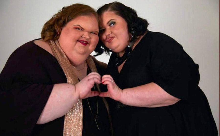 Tammy and Amy put their hands together to make a heart.