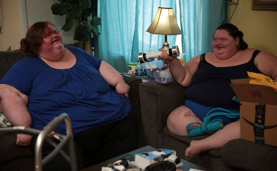 Tammy and Amy unpack a shake weight and other exercise equipment.