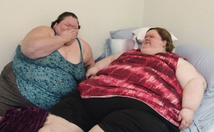Amy and Tammy are laughing in bed.