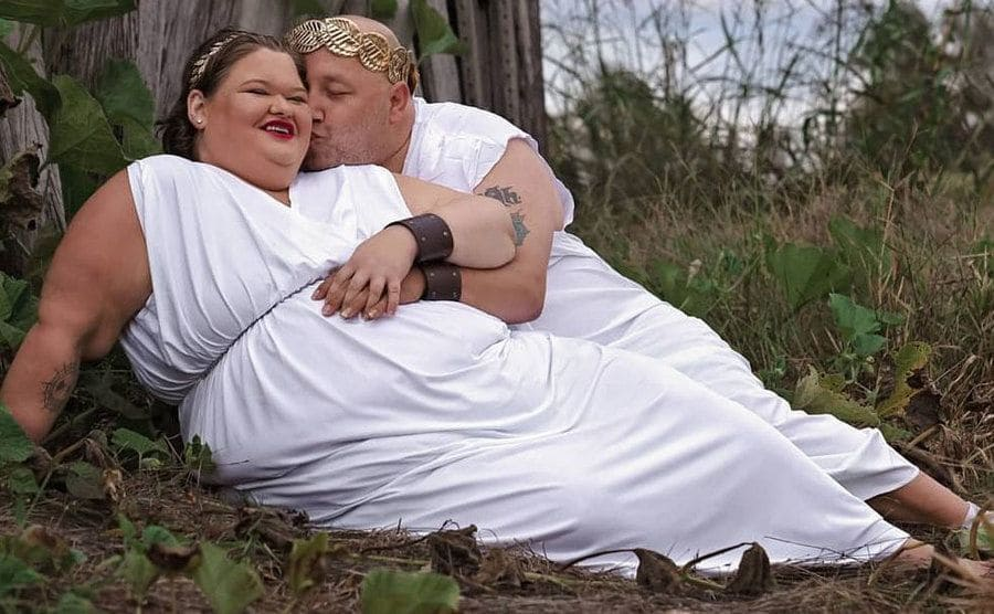 Amy and Michael dress all in white as the pose for pregnancy photos.