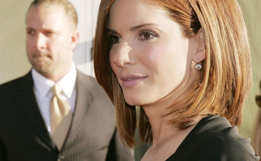 A close-up on Sandra Bullock while Jesse James stands far in the background.