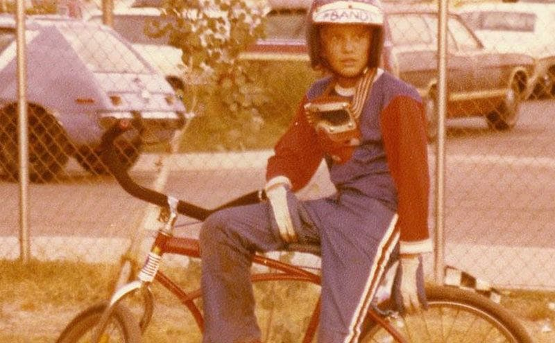 A young Jesse James sits on his bike wearing a helmet and gloves.