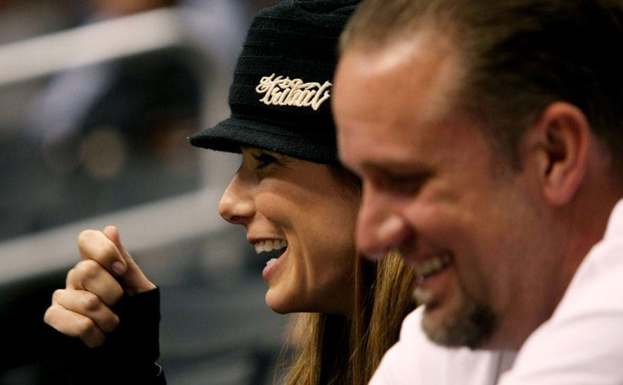 Sandra Bullock and Jesse James are sitting among the crowd at a hockey game.