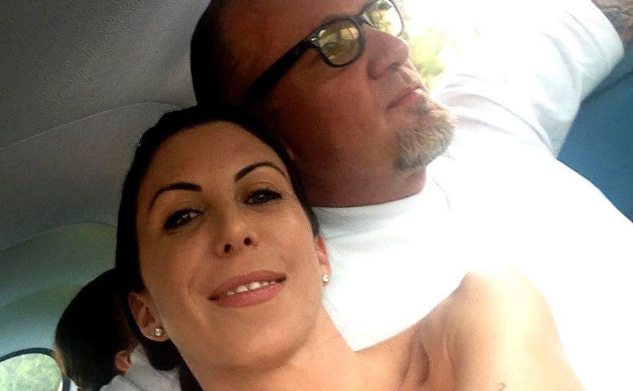 Alexis DeJoria takes a photo next to Jesse James while sitting inside the car.