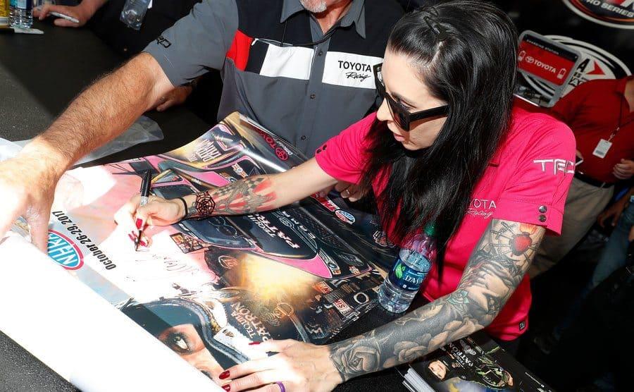Alexis DeJoria autographs a poster.