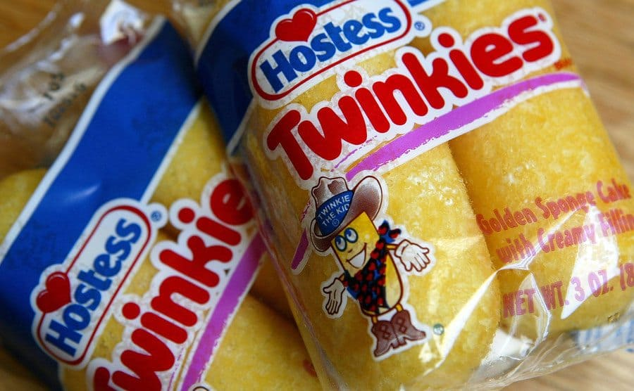 Two packages of Hostess Twinkies sit on a table.