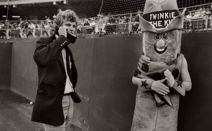 A man stands in a Twinkie the Kid mascot costume.