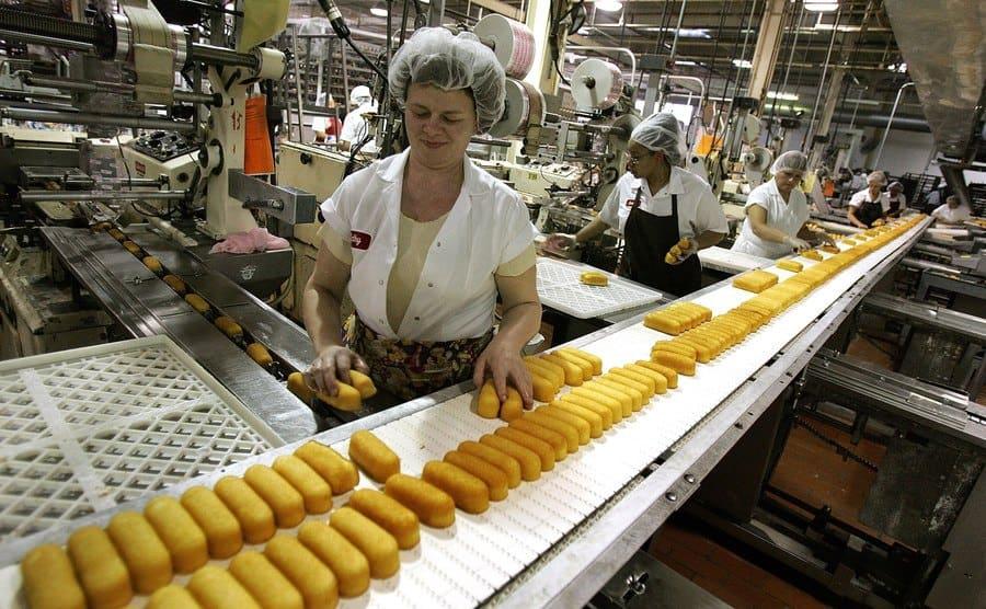 Workers prepare Hostess Twinkies for packaging.
