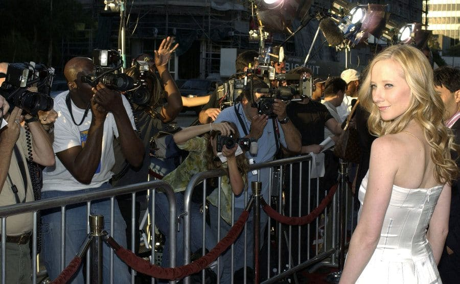 Anne Heche stands in front of reporters and cameramen as they photograph her.