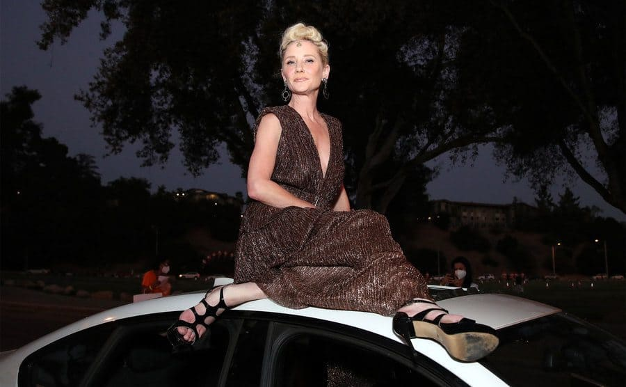 Heche poses on the roof of a car.