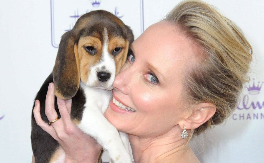 Anne Heche poses as she holds a puppy.