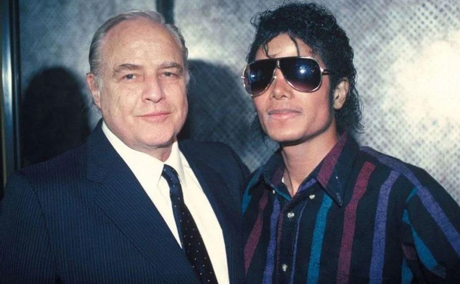 Marlon Brando and Michael Jackson pose together for a portrait.