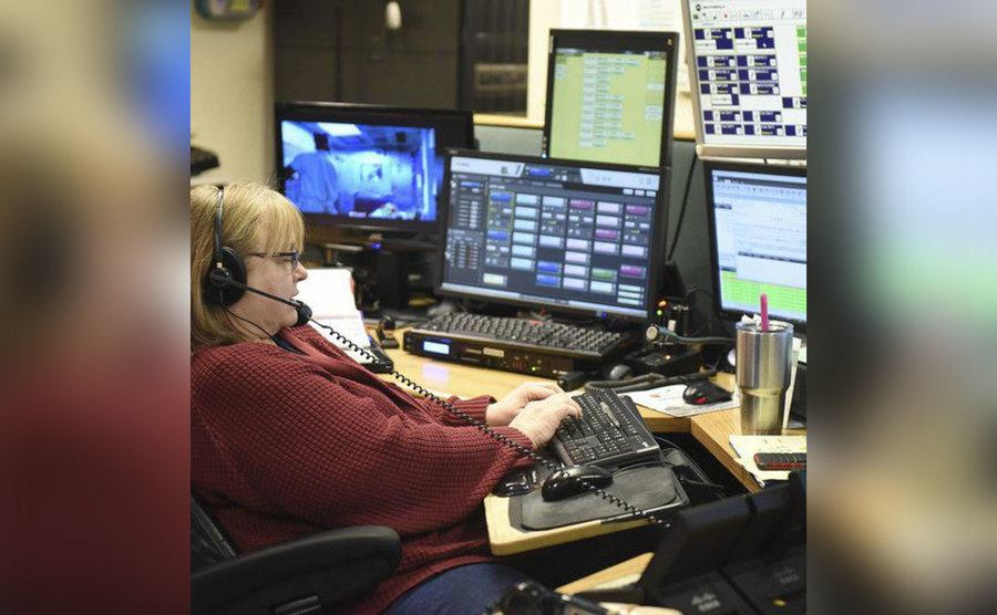 A 911 operator handles a call from her station.