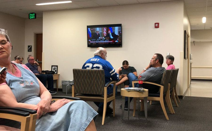 People are seated in an emergency room waiting for the area with a tv.