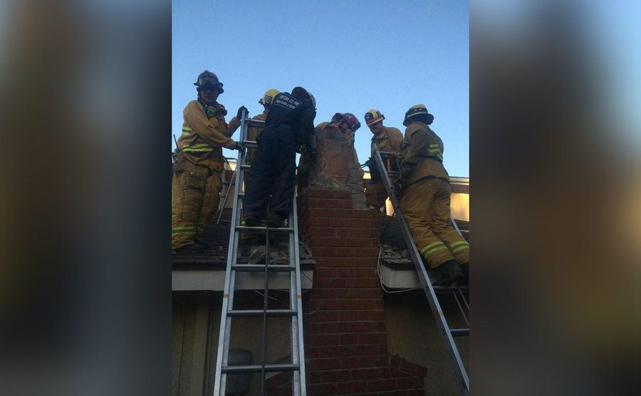 Firefighters help remove a man caught inside a chimney.